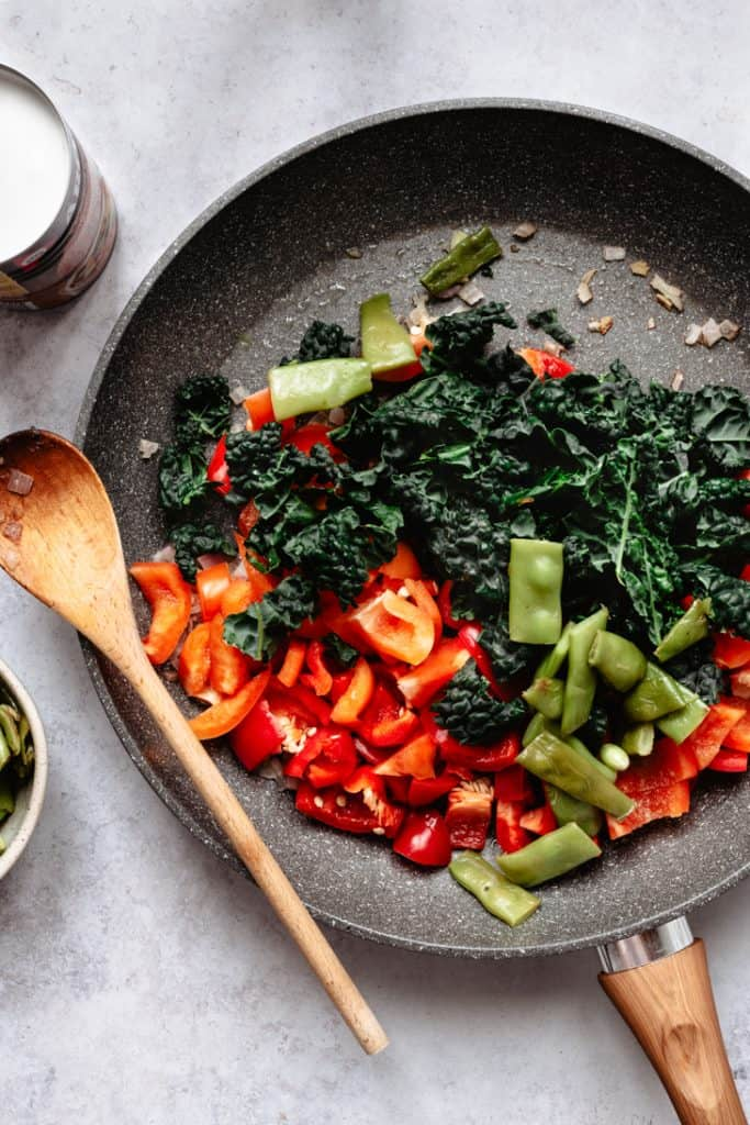 peppers, peas and kale in pan