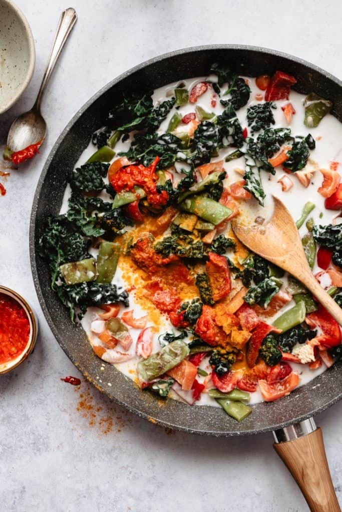 veggies and coconut milk in pan for red curry