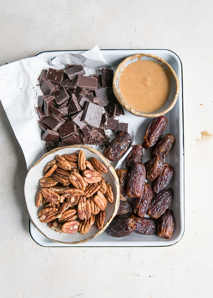 chocolate, peanut butter, pecans and dates on tray