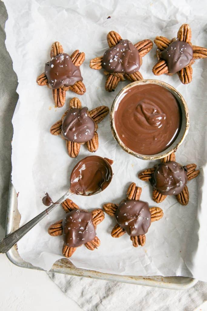 chocolate in bowl with spoon and chocolate turtles on tray