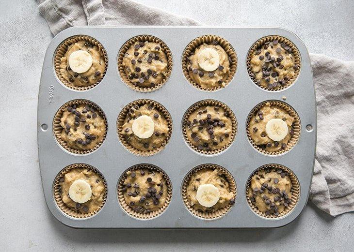 banana muffin batter in muffin pan with chocolate chips