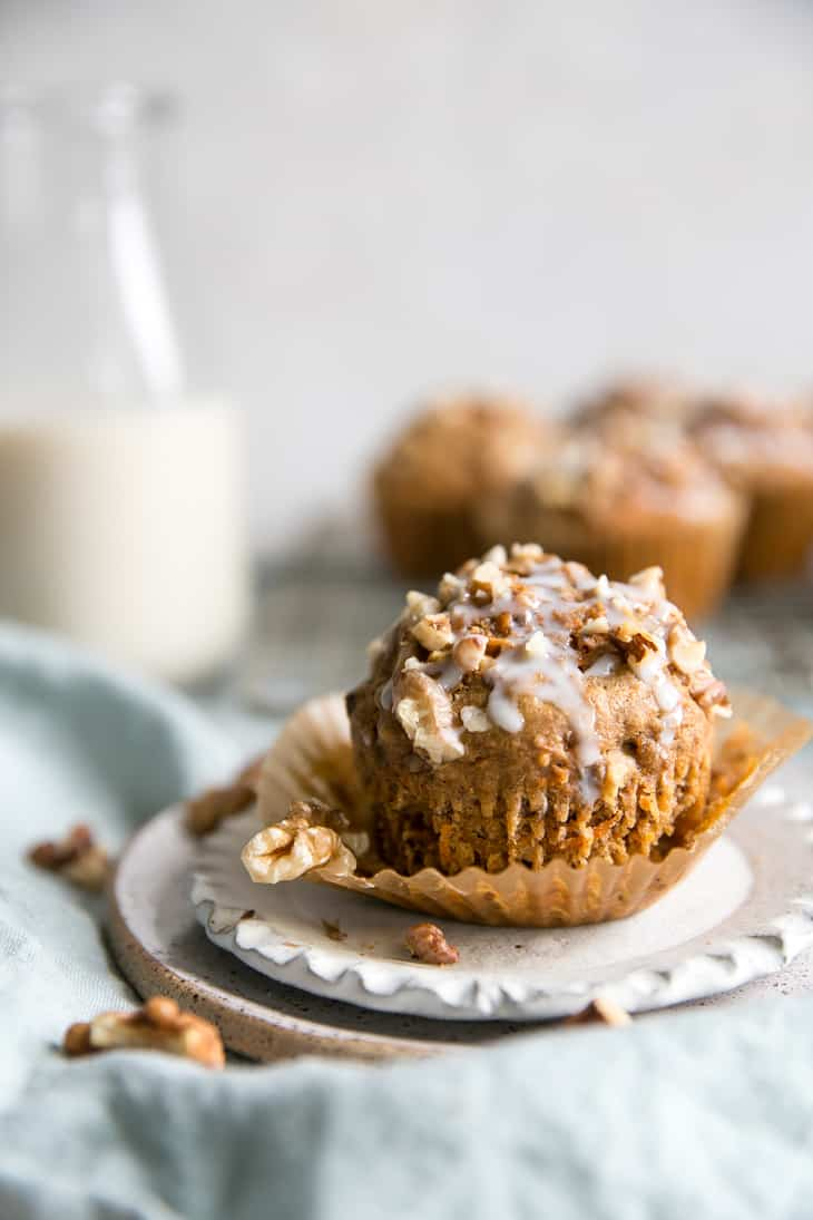Healthy Whole Grain Carrot Muffins with walnuts on cooling rack with coconut glaze