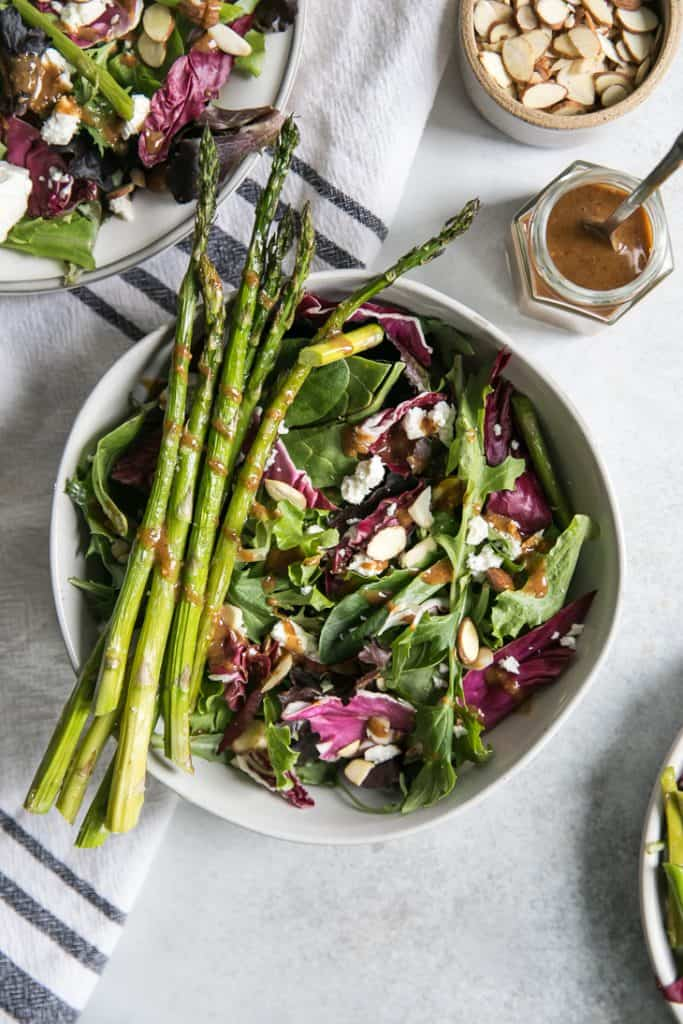 salad in a white bowl topped with asparagus and a drizzled of dressing