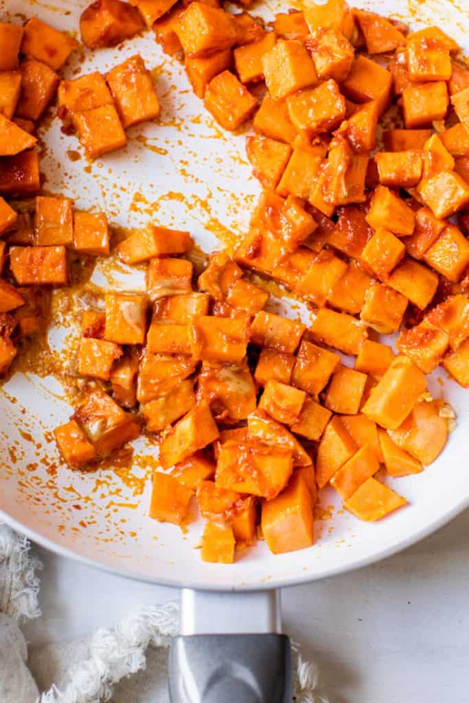 sweet potatoes in skillet with red thai sauce