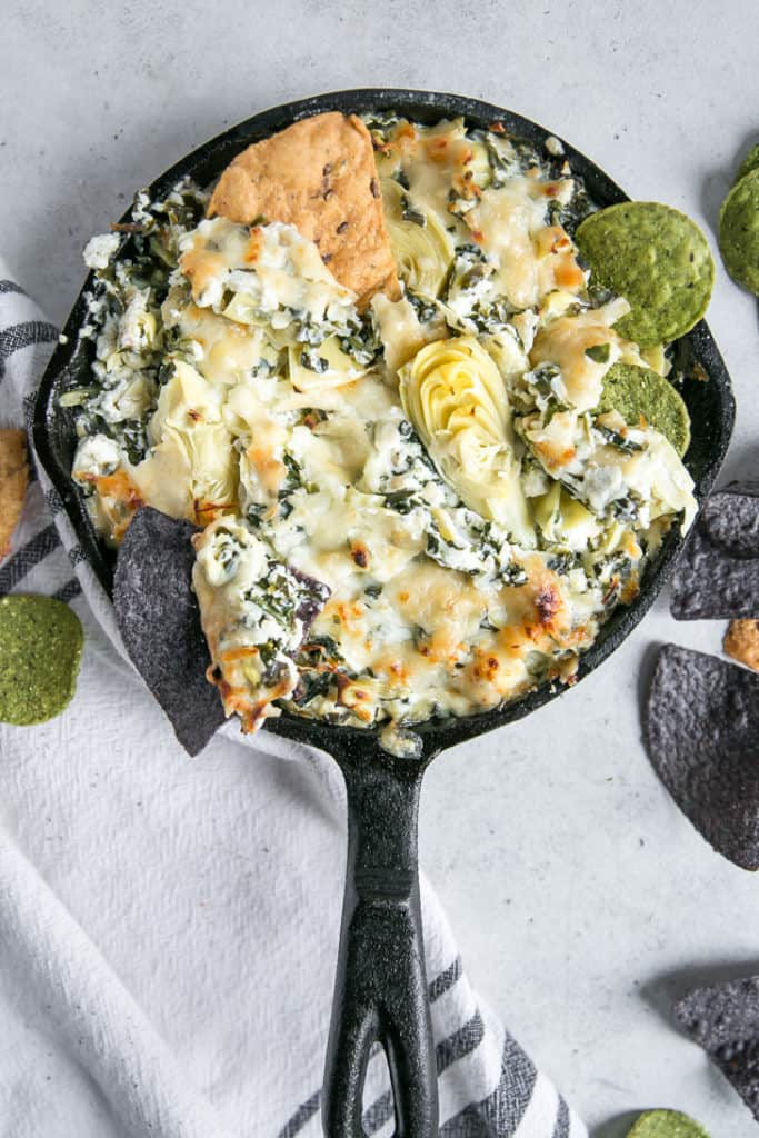 spinach artichoke dip in skillet with chips