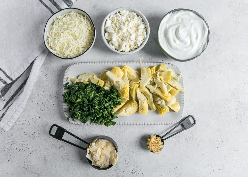 cheese and yogurt in bowls, spinach and artichokes on plate