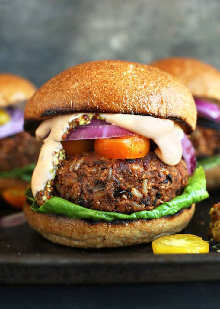 grillable veggie burgers on a tray with tomatoes and sauce