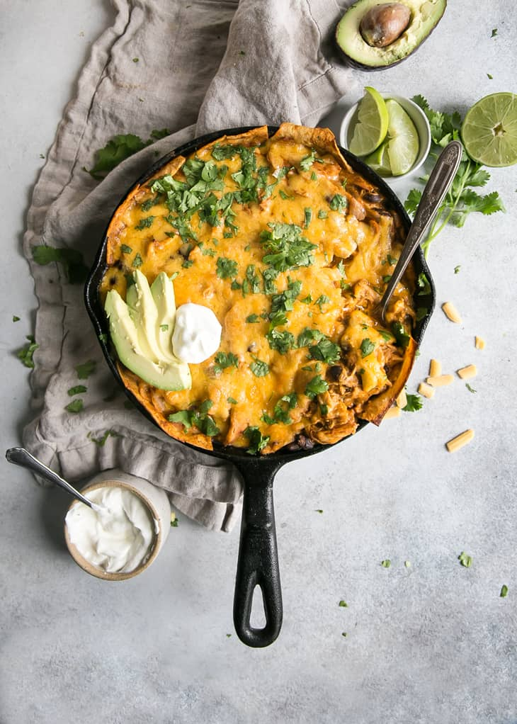 Easy Cheesy Chicken Enchilada in a cast iron Skillet being scooped with sour cream cilantro avocado