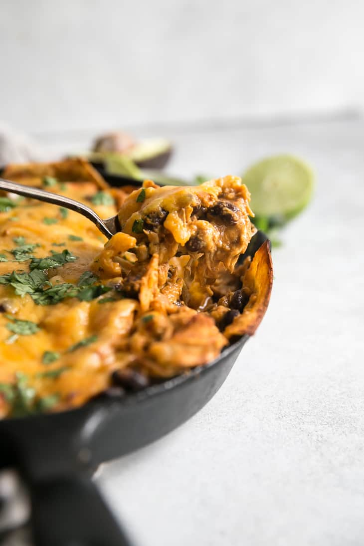 Easy Cheesy Chicken Enchilada in a cast iron Skillet being scooped with sour cream and avocado