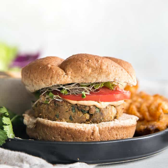 chickpea burger with tomato and sauce on bun