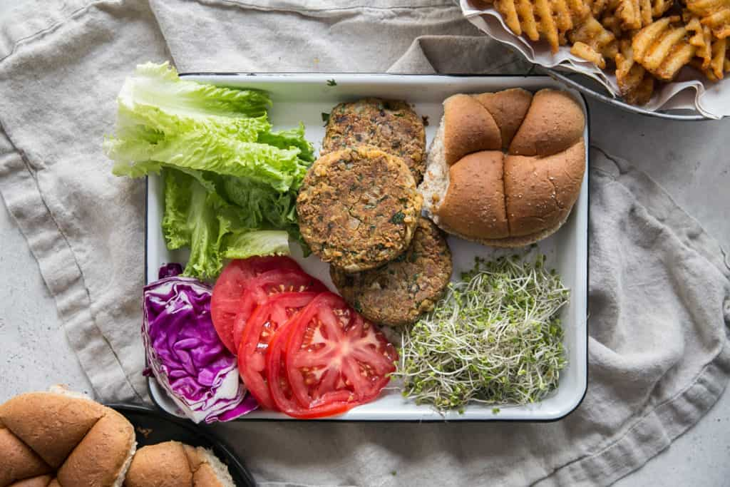 lettuce tomato bean sprouts bun on a white tray for Chickpea Burgers with Chipotle Aioli