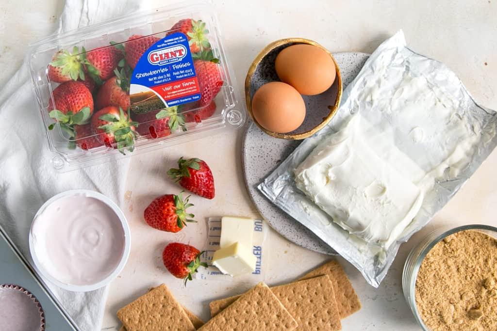 Ingredients, eggs cream cheese strawberries yogurt graham crackers butter