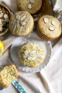 paleo lemon poppy seed muffin on plate with lemon
