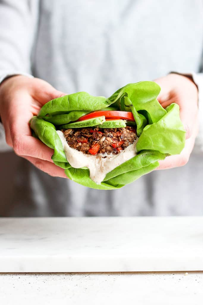 roasted garlic black bean quinoa burger being held in lettuce with avocado tomato and aioli
