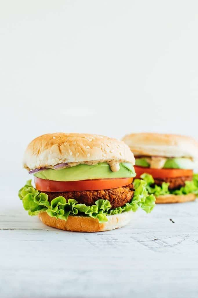tempeh veggie burger with onion lettuce avocado and sauce