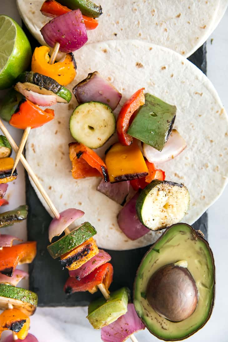 grilled fajita vegetables on skewer with tortilla and avocado