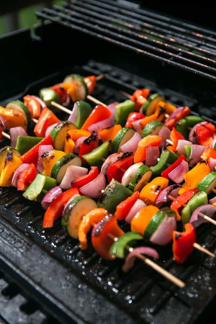 vegetable kabobs cooking on a grill - peppers onions and zucchini