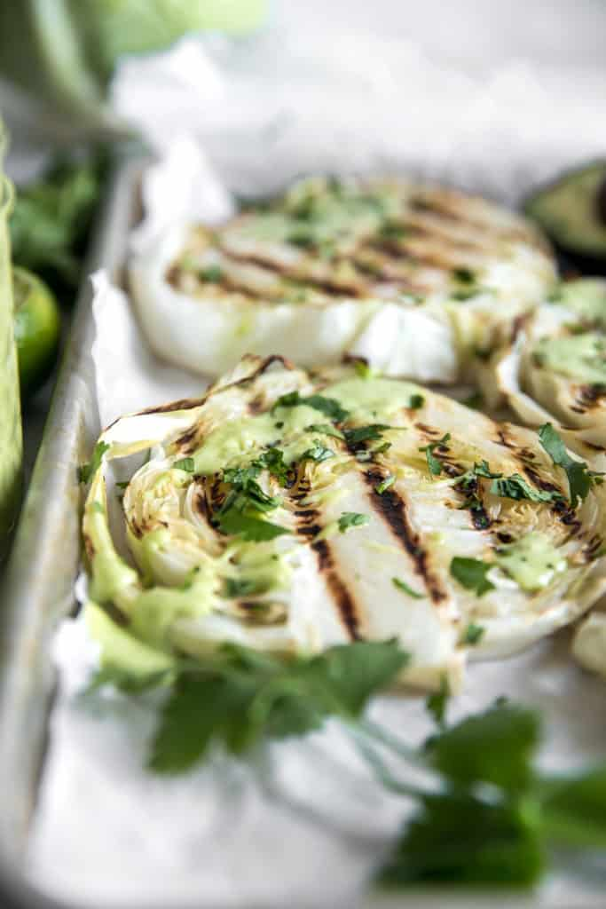 grilled cabbages steaks on a cookie sheet with avocado sauce and cilantro