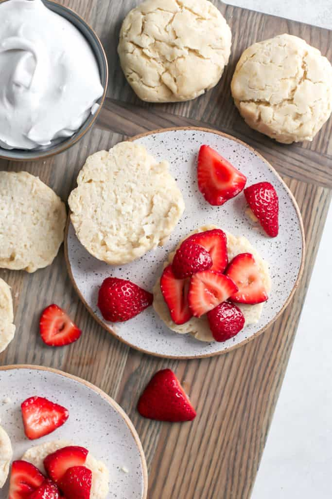 assembling strawberry shortcake on a wooden cutting board