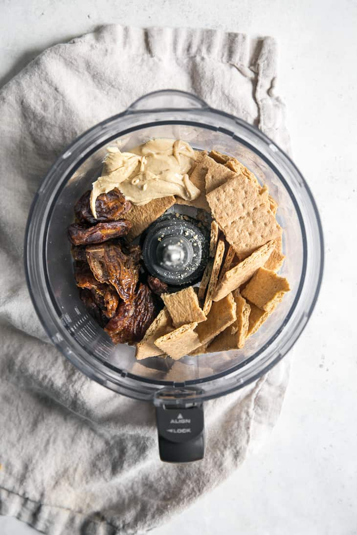 food processor bowl with graham crackers, medjool dates and cashew butter