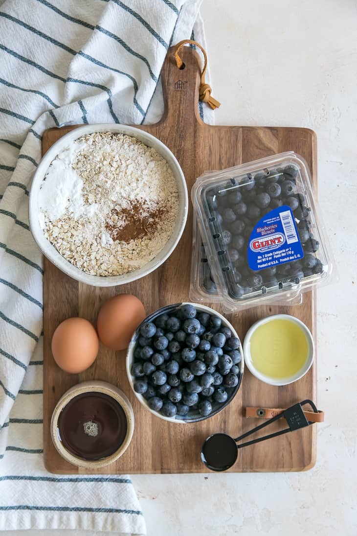 ingredients needed for blueberry oatmeal muffins on wooden cutting board - oats blueberries eggs maple syrup