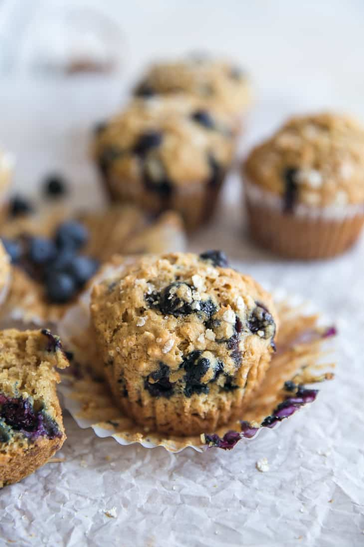 blueberry muffins with oat crumble on an opened muffin liner