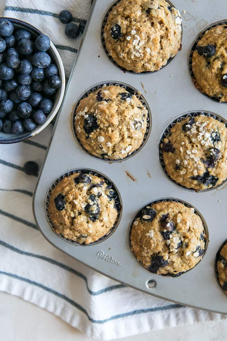 blueberry muffins in muffin tin on a blue and white stripped towel