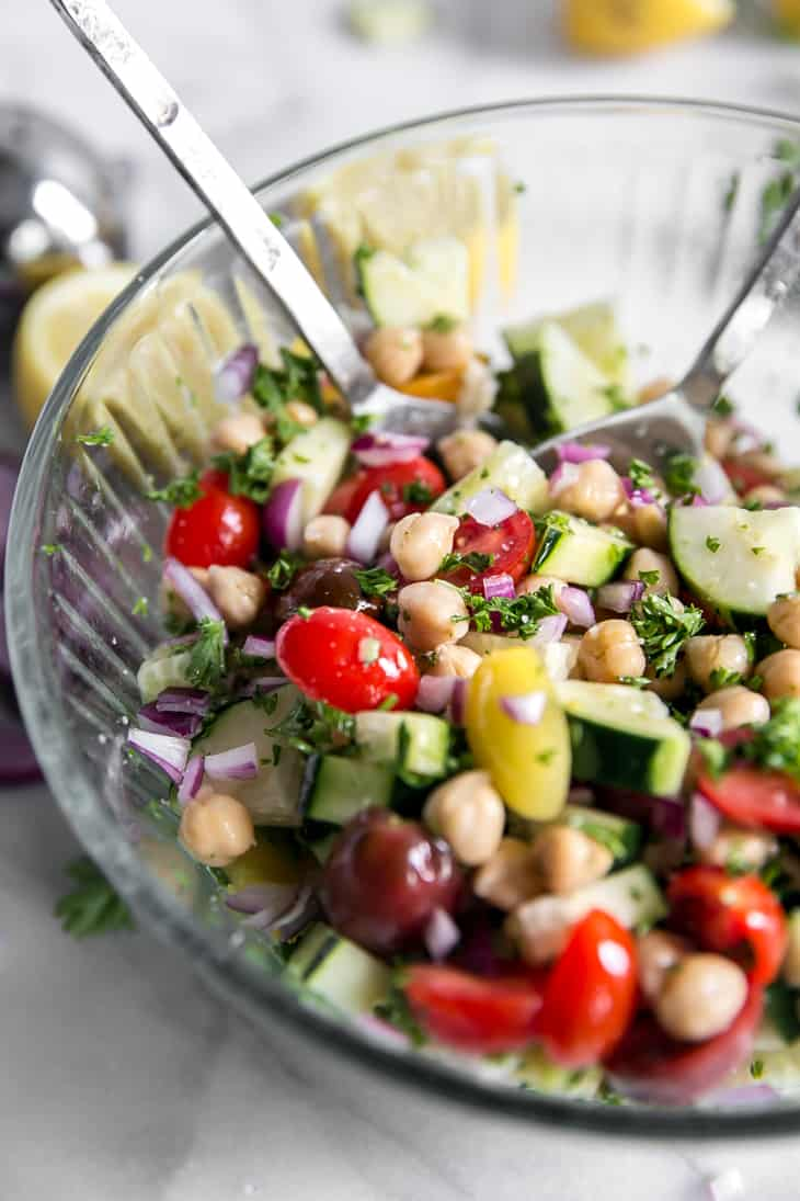 chickpeas, cherry tomatoes and cucumbers mixed in a glass bowl