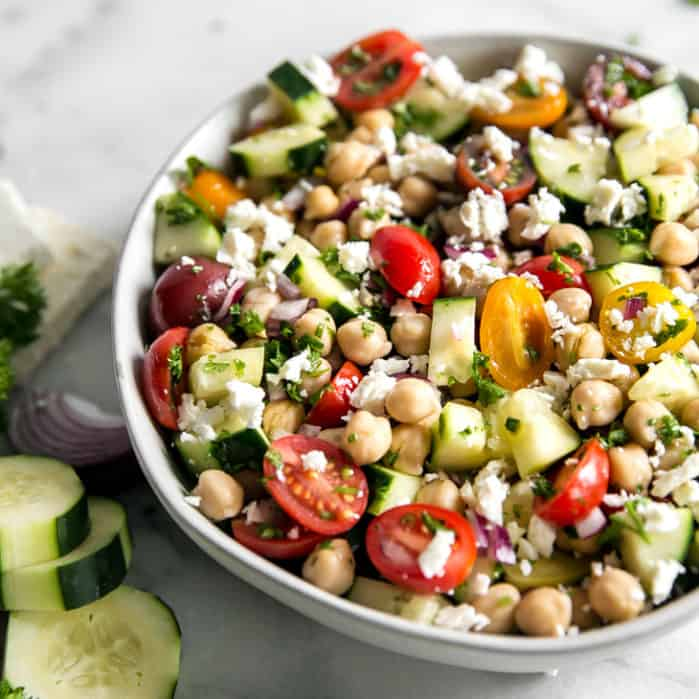 chickpea salad with feta in bowl and cucumbers