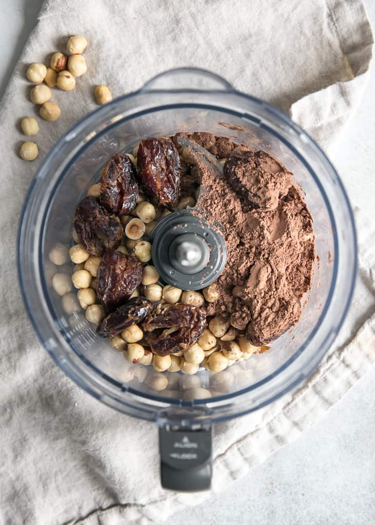 food processor bowl with dates, cacao powder and hazelnuts