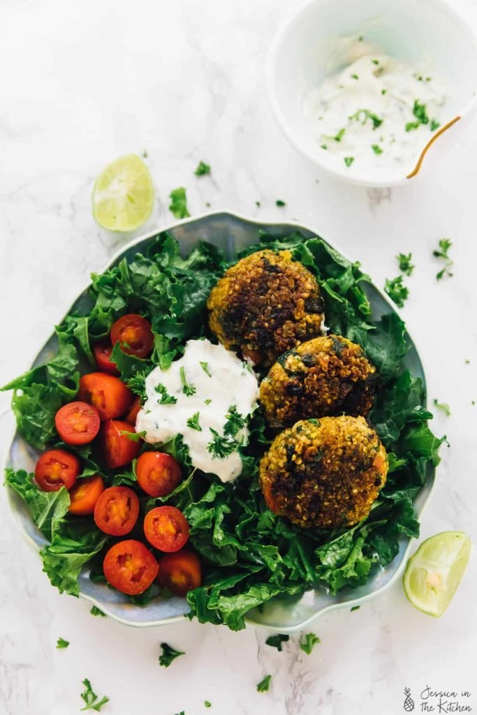 a bed of greens topped with quinoa patties, tomatoes, and vegan yogurt tahini sauce
