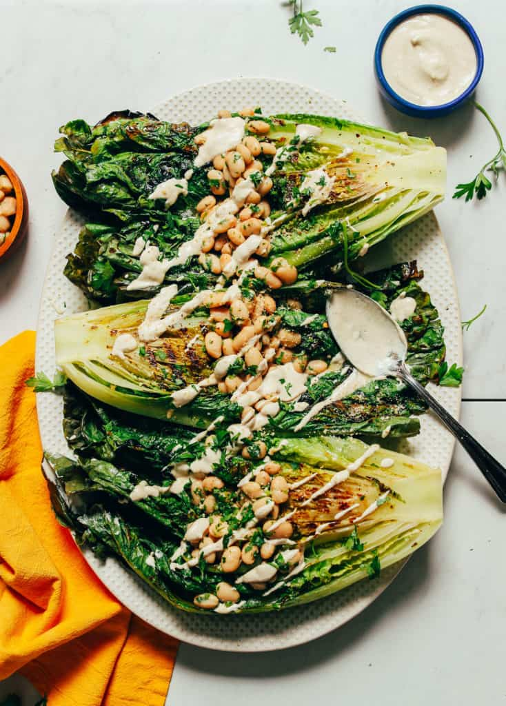grill romaine lettuce topped with white beans and herb sauce on a cream platter