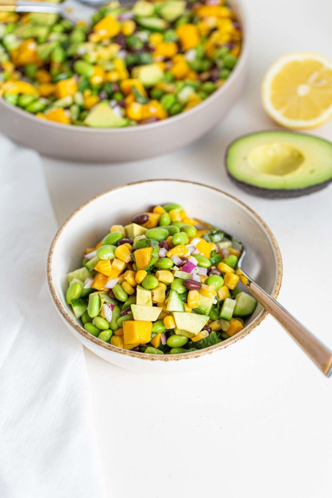 edamame, avocado, corn, and cucumber in a small cream bowl surrounded by lemon and a half avocado