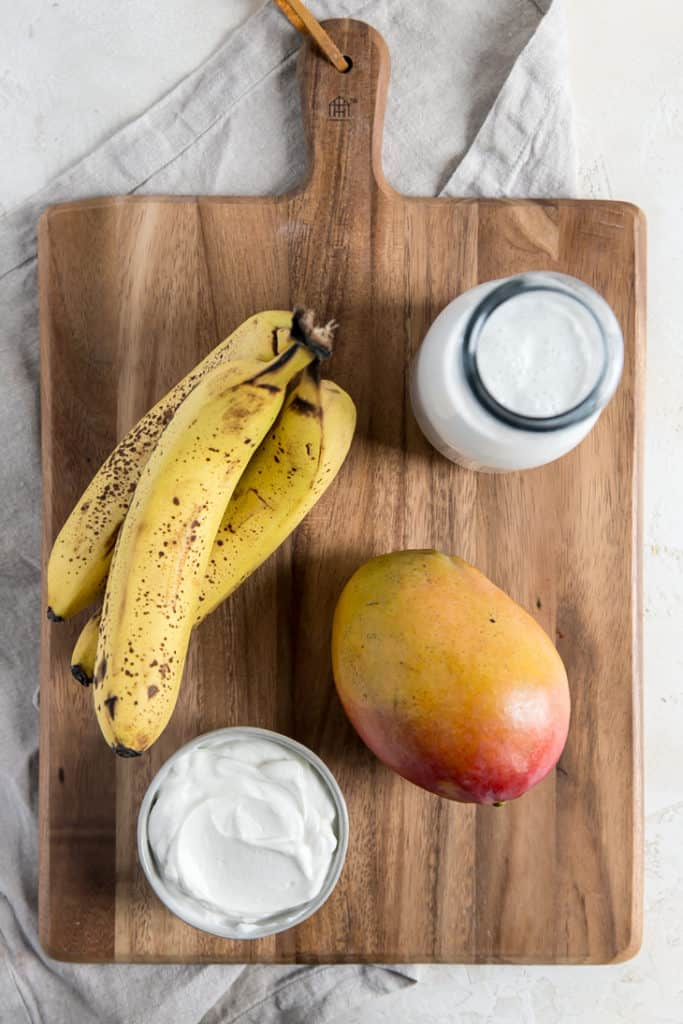 ingredients for mango smoothie on wooden cutting board - yogurt banana mango and coconut milk