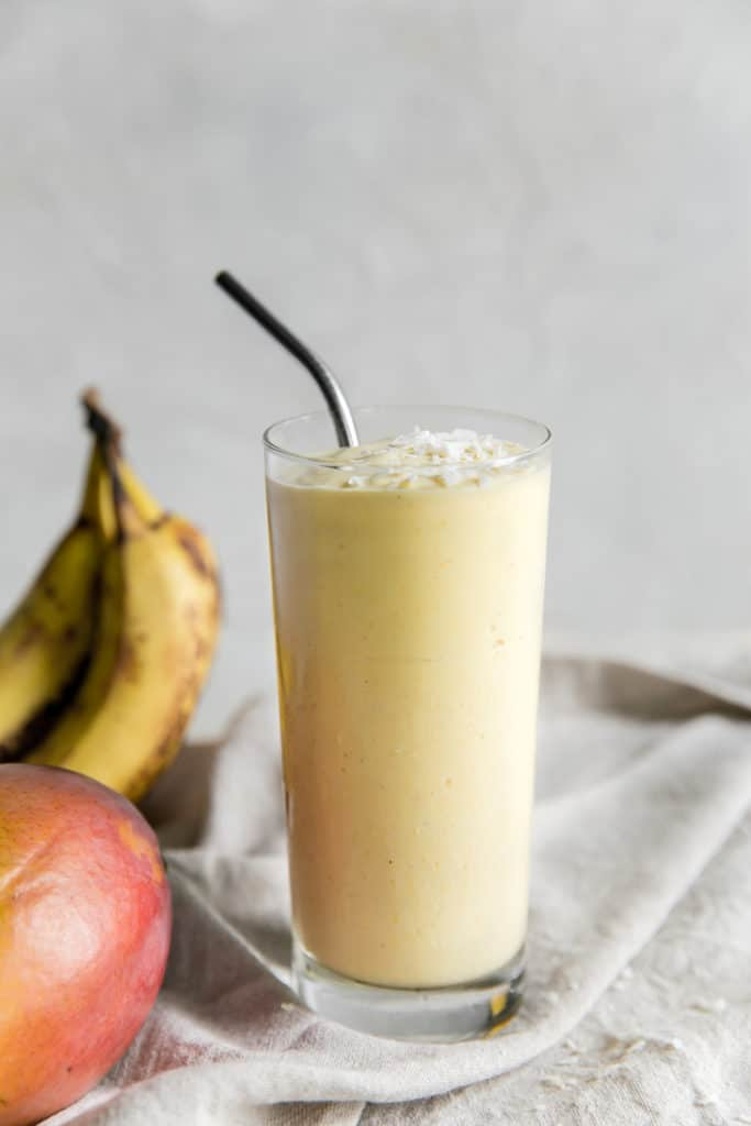 mango smoothie in a glass cup with a metal straw