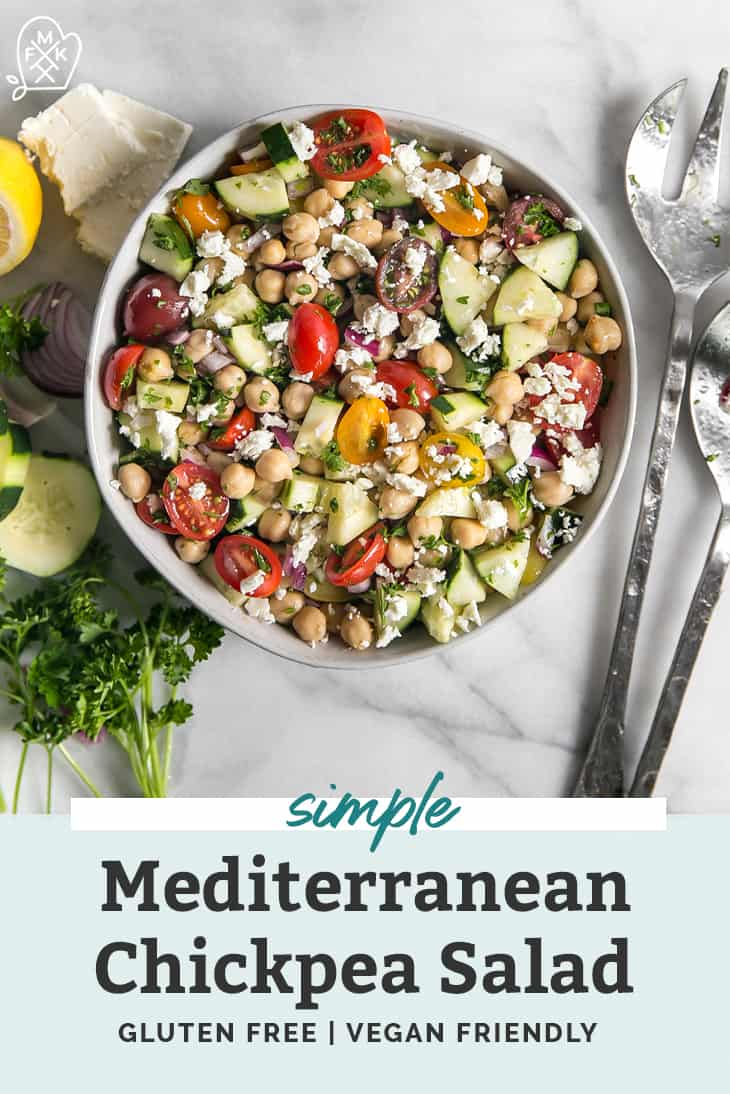 Mediterranean chickpea salad in a white bowl garnished with parsley and feta