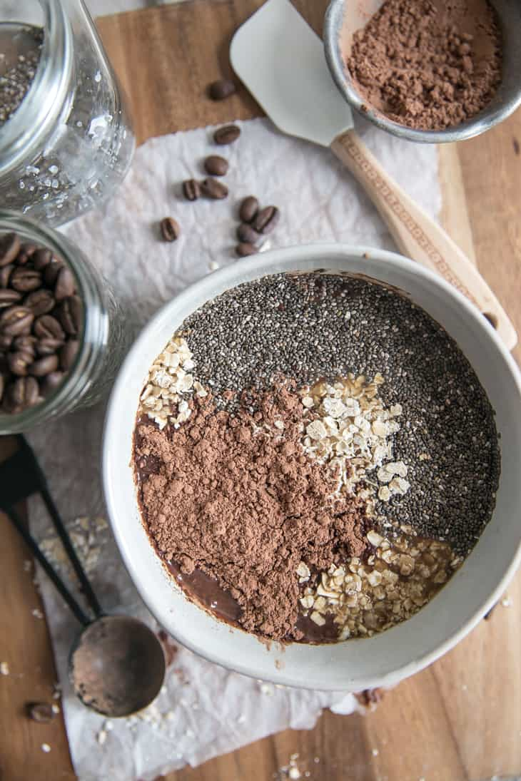 oats cocoa chai seeds and coffee in a white bowl on wood cutting board