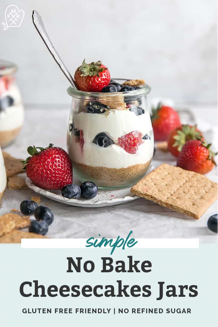No Bake Cheesecakes in jars with strawberries blueberries raspberries and graham cracker crumble