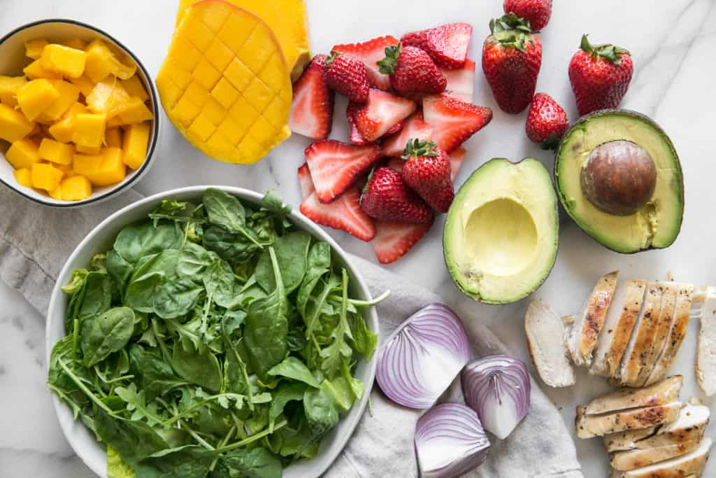 spinach, mango, strawberries, red onion, and grilled chicken on marble board