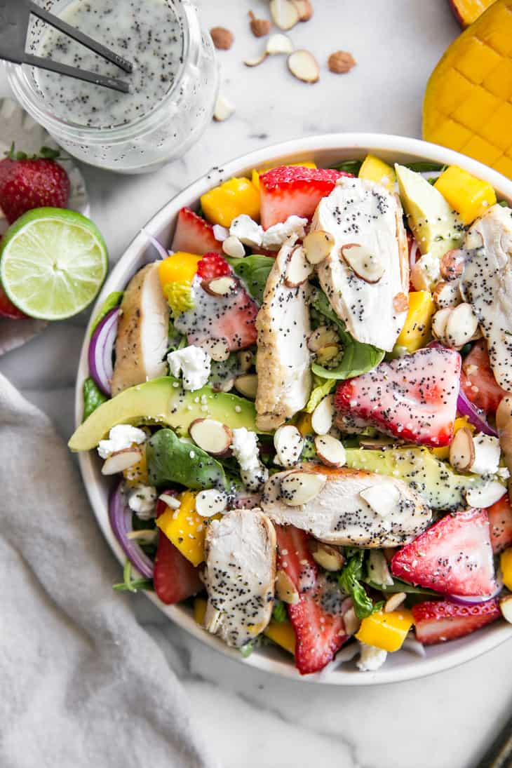 close up of salad plate with avocado, mango, strawberries, grilled chicken and poppy seed dressing
