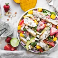 mango strawberry salad on marble board with dressing