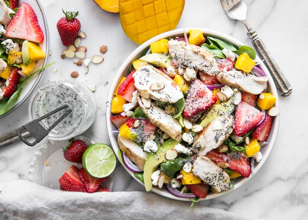 salad with strawberries, avocado, and mango on marble board with poppy seed dressing