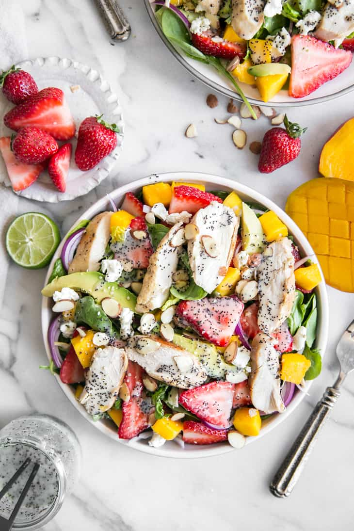 strawberry mango salad with grilled chicken and poppy seed dressing on plate