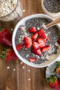 chia seeds and strawberries in bowl on wood board