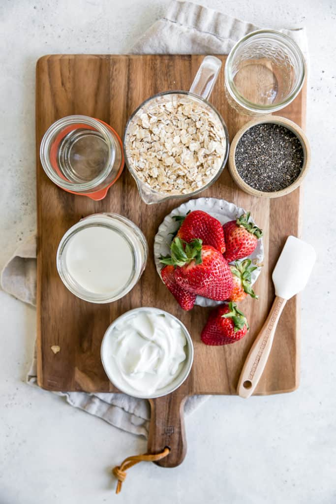 oats, yogurt, milk, chia seeds and strawberries on wood board