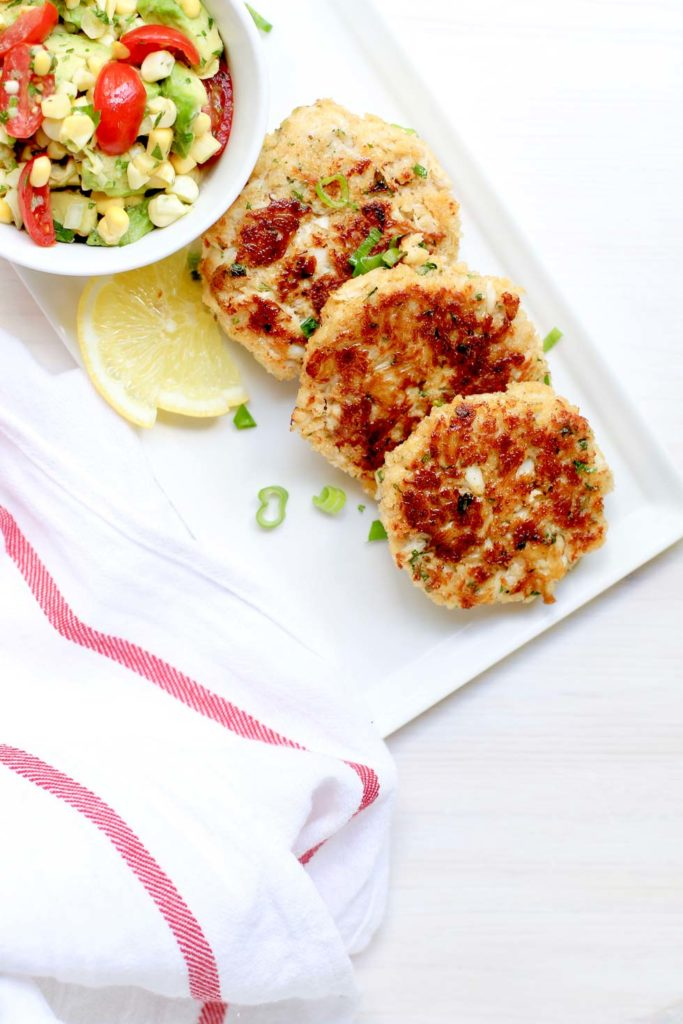 crab cakes and avocado corn salsa on a white rectangular plate