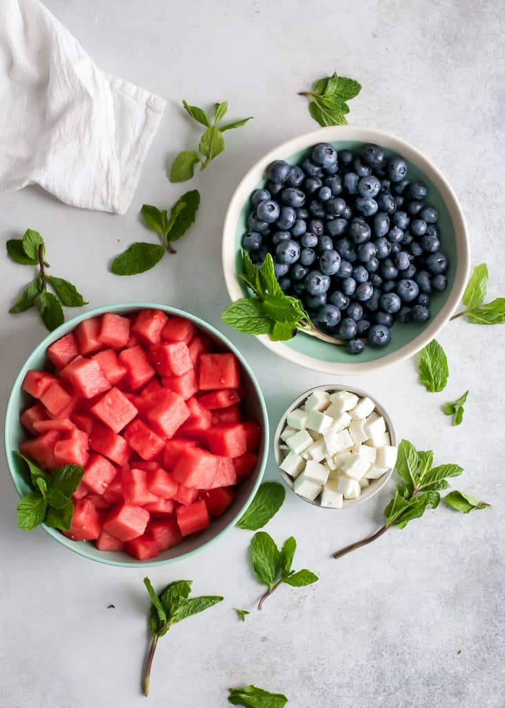 bowl of cubed watermelon, fresh blueberries, cubed feta in small bowl and scattered mint leaves