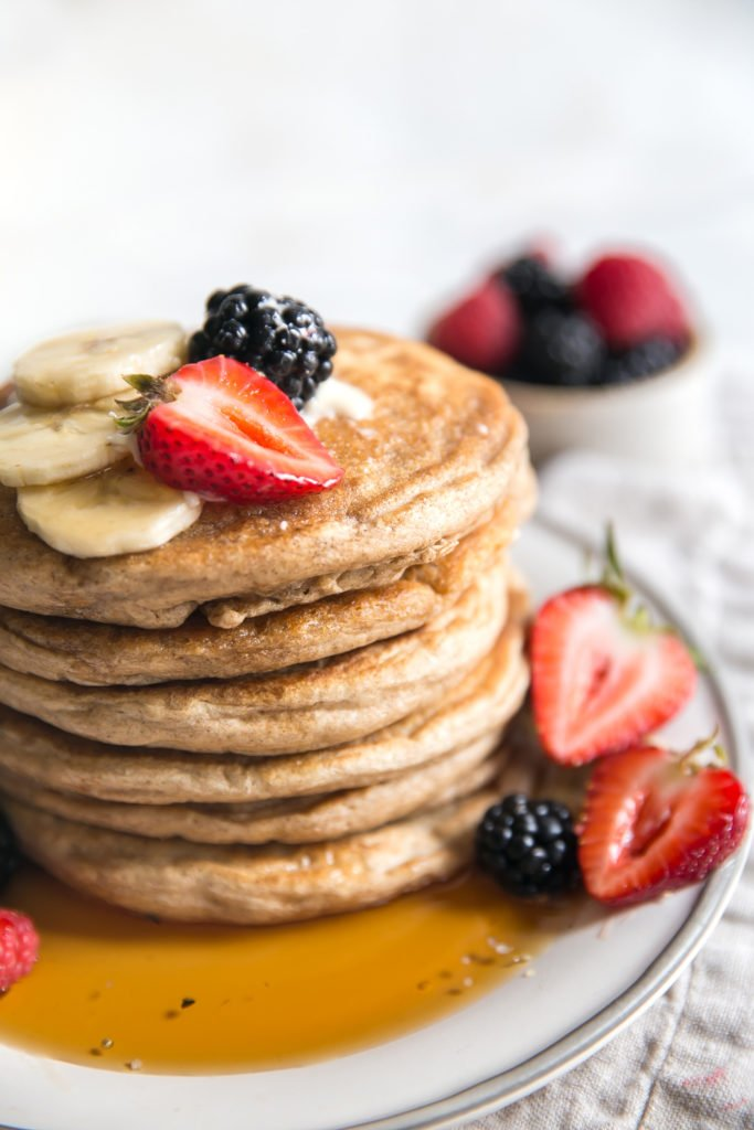 whole wheat pancakes stack on plate with maple syrup