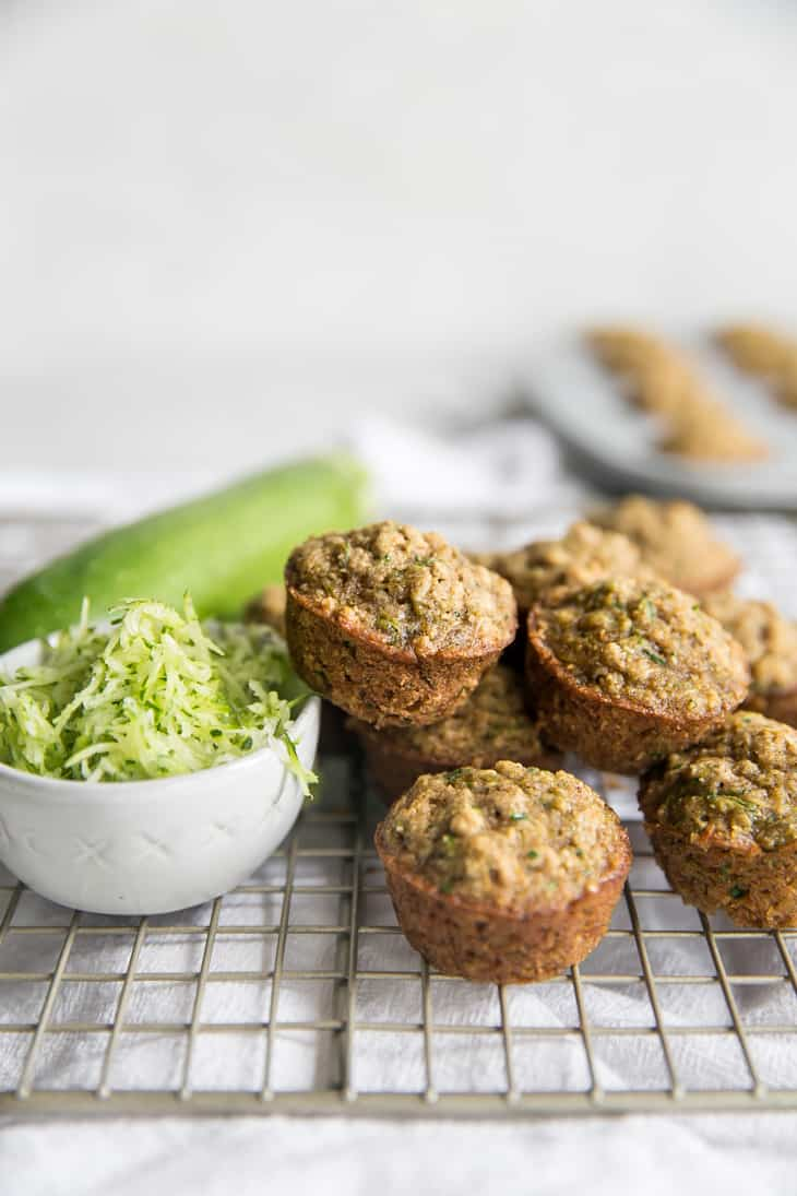 mini gluten free zucchini muffins and a  small bowl of zucchini on top of a wire cooling rack