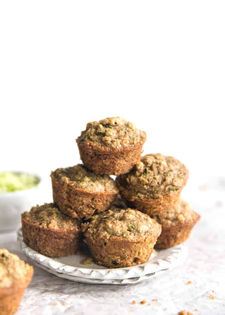 mini zucchini muffins stacked on a small cream plate